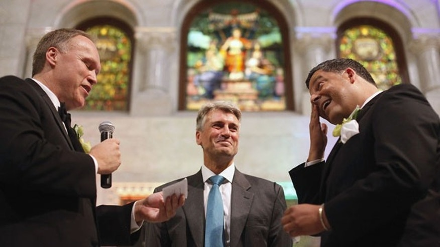 FILE - In this Aug. 1, 2013 file photo, Minneapolis Mayor R.T. Rybak, center, officiates at the wedding of Al Giraud, right, and his partner Jeff Isaacson at the Minneapolis City Hall. They were the first gay couple legally married in Minnesota. (AP Photo)