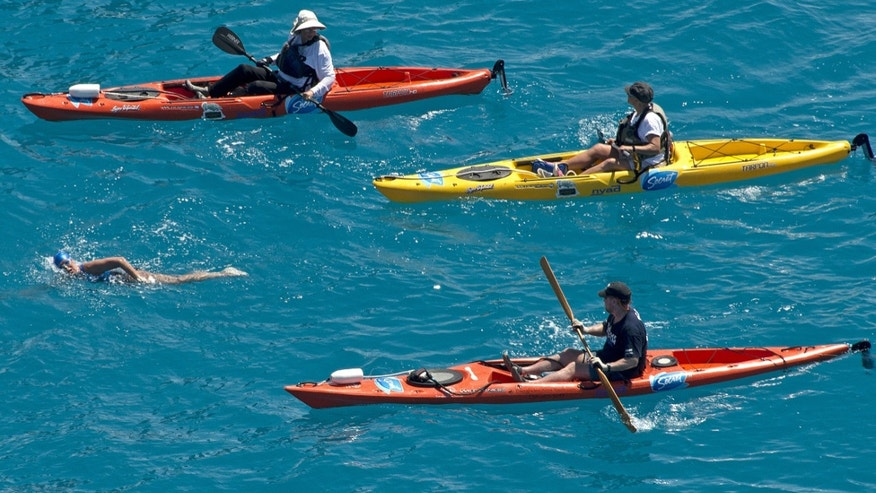 In this photo provided by the Florida Keys News Bureau, Diana Nyad, positioned about two miles off Key West, Fla., Monday, Sept. 2, 2013, is escorted by kayakers as she swims towards the completion of her approximately 110-mile trek from Cuba to the Florida Keys. Nyad, 64, is poised to be the first swimmer to cross the Florida Straits without the security of a shark cage. (AP Photo/Florida Keys News Bureau, Andy Newman)