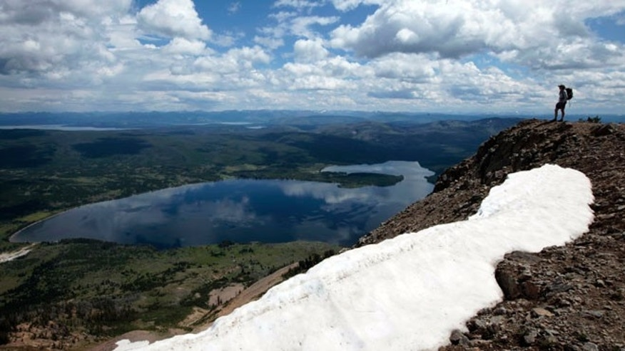FILE: August 9, 2011: A hiker stands on top of Mount Sheridan, overlooking Heart Lake in the Red Mountains of Yellowstone National Park, Wyoming.