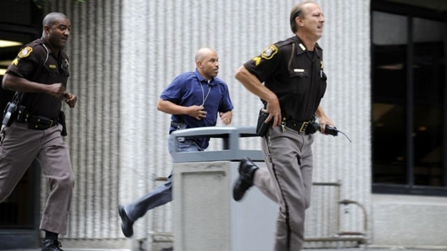 September 9, 2013: Wayne County Sheriff's Department personnel rush from the the Frank Murphy Hall of Justice to look for an escaped prisoner in Detroit. (AP Photo/Detroit News)