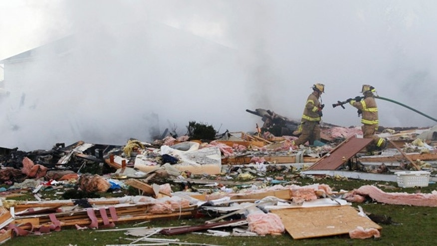 Sept. 17, 2013: Firefighters douse hotspots following a house explosion in Stony Ridge, Ohio.