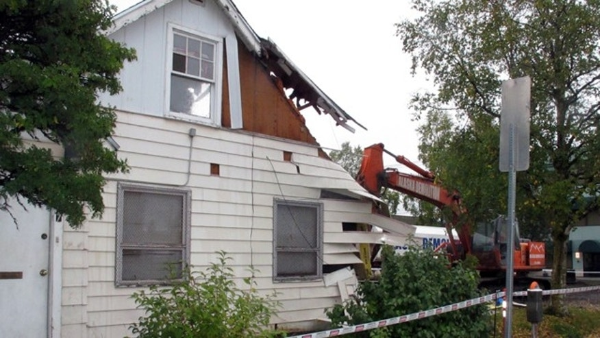Sept. 19, 2013: A demolition crew knocks down an abandoned house in Anchorage, Alaska.