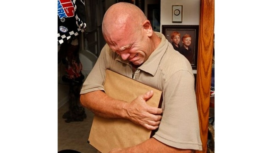Sept 18, 2013: Steve Woods cries in Clarksville Tenn., as he holds a photo of his father's medals, Staff Sgt. Lawrence Woods who has been missing in action since Oct. 24, 1964, when his plane was shot down near the border of Vietnam and Cambodia.