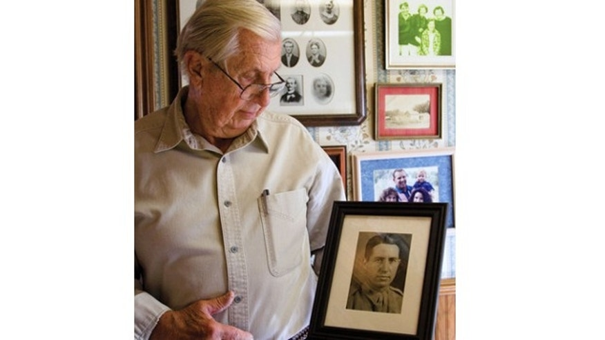 UNDATED: Jerry Hoblit holds a picture of his father, Col. Noel Hoblit, who was killed in a military plane crash and missing for 60 years. The wreckage was discovered in June 2012 in Alaska.