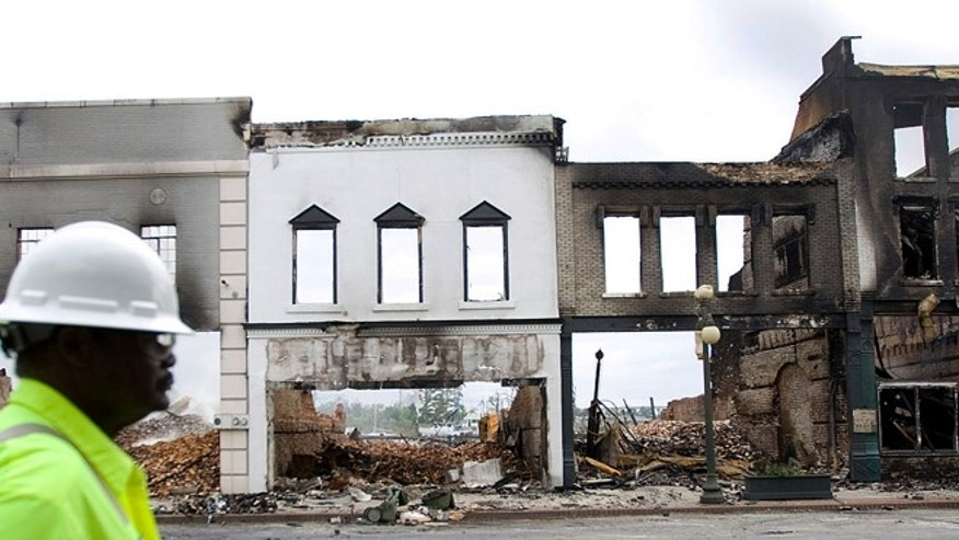 Sept. 26, 2013: People walk past what remains of buildings in Georgetown, S.C.'s business district after a Wednesday morning fire destroyed several buildings, mostly small mom-and-pop business.