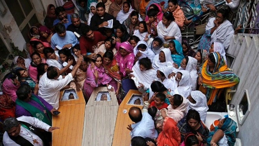 Sept. 24, 2013: Pakistani Christians mourn in a family home as they gather around the coffins of their relatives, who were killed in Sunday's suicide attack on a church, in Peshawar.