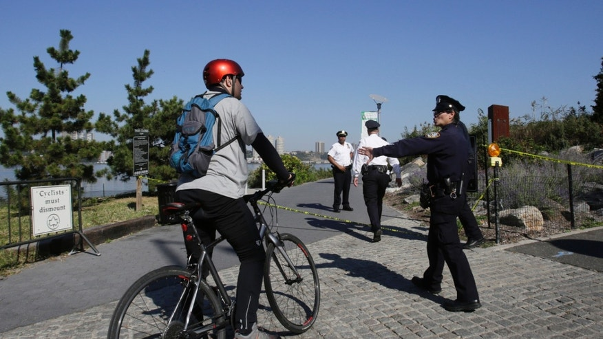 A police officer stops a bicyclist from entering a section of New York's Riverside Park South where a man earlier went on a rampage stabbing five people, including a one-year-old, early Tuesday, Oct. 1, 2013. The suspect, who appeared to be homeless and emotionally disturbed, was taken into custody, said Police Commissioner Raymond Kelly. All the victims were expected to survive, though one of the women was listed in critical condition. (AP Photo/Mark Lennihan)