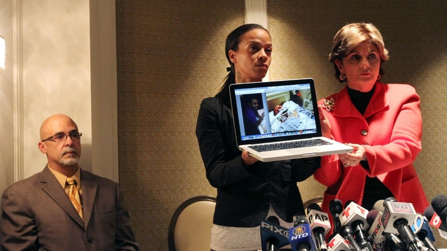 Dayana Mejia, center, and attorney Gloria Allred, right, hold up a laptop with images of Mejia's partner, Edwin Mieses Jr., during a news conference in New York, Friday, Oct. 4, 2013. Mejia was struck by an SUV during a bloody weekend confrontation with a throng of motorcyclists. Seated at left is Mieses' father, Edwin Mieses Sr. Shown on the laptop are images of Mieses Jr., before and after the incident. (AP Photo/Tina Fineberg)