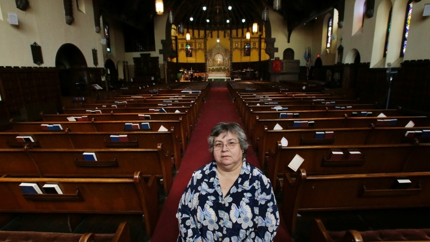 "Armantina Pelaez, a former crisis counselor at St. Mary's Hospital, in Paterson, N.J., stands in Paterson's Saint Paul's Episcopal Church, Monday, Sept. 23, 2013. In early 2011, St. Mary's Hospital CEO told employees that the retirement plan's trust was severely underfunded, acknowledging the hospital had not put aside any money for their pensions in more than a decade. ""I was very angry. I felt betrayed, not only by the health care system, but by the Sisters of Charity and I got betrayed by the church,"" said Pelaez, about St. Mary's, which quietly converted its federally insured pension plan to an uncovered church plan in 2001. (AP Photo/Mel Evans)"