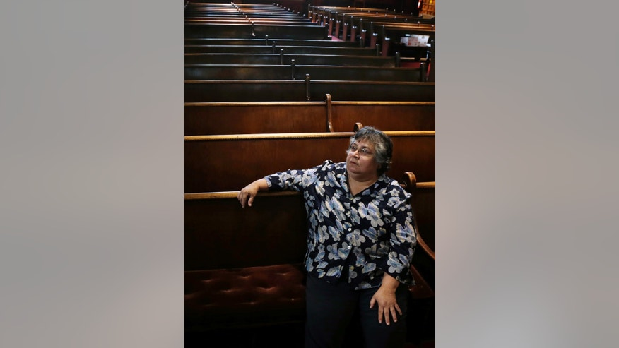 "Armantina Pelaez, a former crisis counselor at St. Mary's Hospital, in Paterson, N.J., sits in Paterson's Saint Paul's Episcopal Church, Monday, Sept. 23, 2013. ""I was very angry. I felt betrayed, not only by the health care system, but by the Sisters of Charity and I got betrayed by the church,"" said Pelaez, about St. Mary's, which quietly converted its federally insured pension plan to an uncovered church plan in 2001. The hospital's pending purchase by a for-profit company will see Pelaez and others get a fraction of their expected pensions. (AP Photo/Mel Evans)"