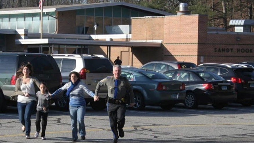 FILE - In this Friday, Dec. 14, 2012, file photo provided by the Newtown Bee, a police officer leads two women and a child from Sandy Hook Elementary School in Newtown, Conn. (AP Photo/Newtown Bee)