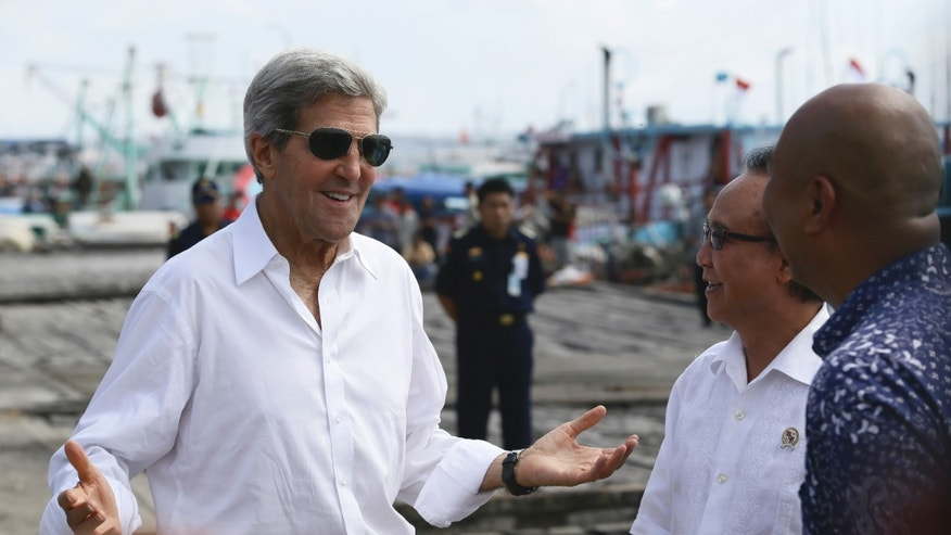 "U.S. Secretary of State John Kerry speaks to officials during a visit to a tuna packaging factory in Bali, Indonesia, Sunday, Oct. 6, 2013. Kerry said Sunday that a pair of U.S. military raids against militants in North Africa sends the message that terrorists ""can run but they can't hide."" Kerry, in Bali for an economic summit, was the highest-level administration to speak about the operations yet.  (AP Photo)"