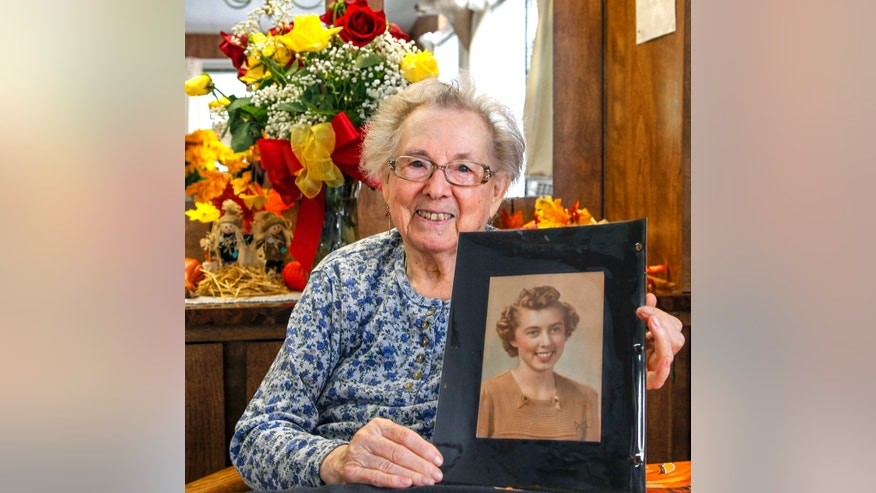 In this Oct. 2, 2013 photo, Ruby Hazen of Toutle, Wash., poses with a photo that was returned after seventy years in Toutle, Wash. Seventy years later, the pretty red-haired girl has her portrait back. Jim Williams of Springfield, Ill., says he went dancing with the young woman who was then Ruby Ruff in 1943 in Portland, Ore. They were both 22; he was in the Coast Guard. She invited him to her house for lemonade and he stole a photo of her that he saw there. Williams mailed back the photo, along with a dozen roses, and the two friends chatted by Skype. (AP Photo/The Daily News, Bill Wagner)