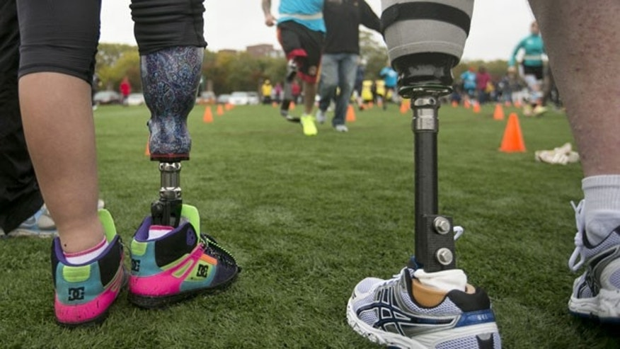 October 6, 2013: Andres Burgos, of Foxborough, Mass., top, runs toward Jordan Simpson, 14, of Berlin, Mass., legs only at left, and Jim Kane, of Mansfield, Mass., legs only at right, using a prosthetic leg during a running clinic for challenged athletes, in Cambridge, Mass. (AP Photo)
