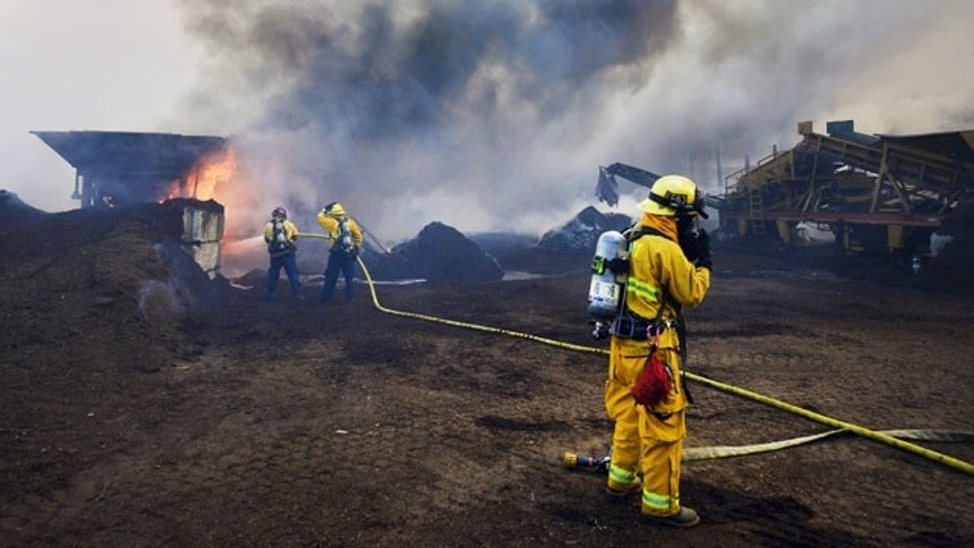 October 6, 2013: Newport Beach and Laguna Beach firefighters work to put out a mulch pile at a nursery near Santiago Canyon in Orange County, Calif. (AP Photo)
