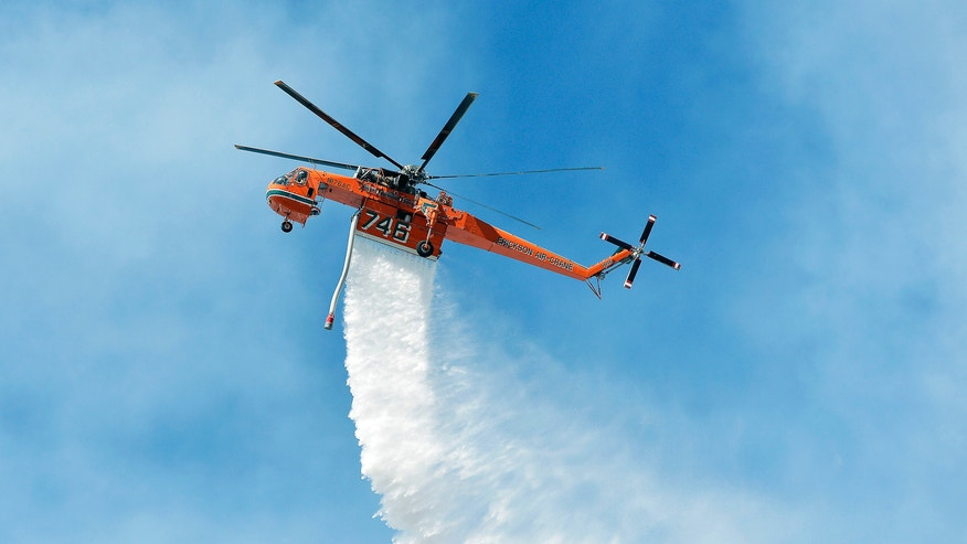 A Sikorsky firefighting helicopter makes a water drop on flames above Baker Canyon in Orange County, Calif. Sunday, Oct. 6, 2013. A mulch pile fire reported late Sunday morning quickly spread to surrounding wild vegetation, said Orange County Fire Authority Capt. Steve Concialdi. No homes were threatened.(AP Photo/The Orange County Register, Stuart Palley)   MAGS OUT; LOS ANGELES TIMES OUT