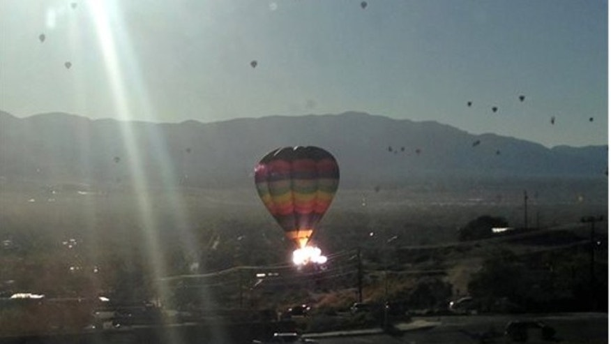 "Oct. 9, 2013: In this photo provided by the Catalyst, the balloon ""New Mexico Sunrise"" strikes a power line after launching during mass ascension at the 2013 Albuquerque International Balloon Fiesta in Albuquerque, N.M."