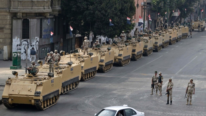 FILE - In this Friday, Aug. 16, 2013, file photo, Egyptian army soldiers take their positions on top and next to their armored vehicles to guard an entrance of Tahrir Square, in Cairo. U.S. officials said Wednesday, Oct. 9, 2013, that the Obama administration is poised to slash hundreds of millions of dollars in military and economic assistance to Egypt. The U.S. has been considering such a move since the Egyptian military ousted the country's first democratically elected leader in June. (AP Photo/Hassan Ammar, File)