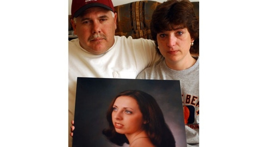 FILE 2003: John and Kandi Burns hold a portrait of their daughter Samantha Burns at their home in West Hamlin, W.Va.