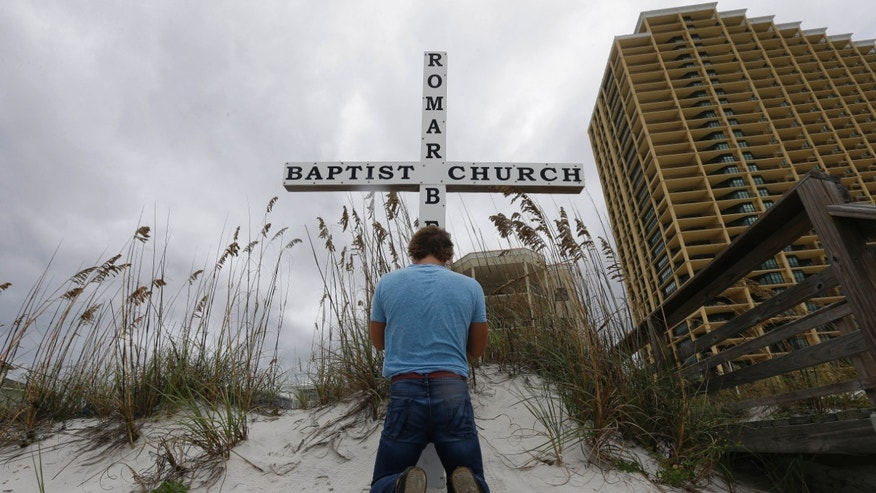 "Dark skies from rain spawned by tropical storm Karen hang over surfer Davey Jones as he prays at the foot of a cross erected on the beach by the Romar Beach Baptist Church in Orange Beach, Ala., Sunday, Oct. 6, 2013.  ""I have never been inside, but I come here to  pray everyday and for the sanctuary and peace this place offers. It is my safe place,"" Jones said about his favorite place in the world. The hurricane proof church provides shelter during storms for it's members and others in need. (AP Photo/Dave Martin)"