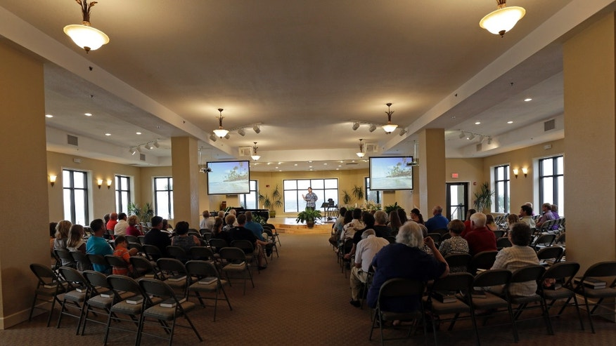Churchgoers listen to a sermon at the Romar Beach Baptist Church in Orange Beach, Ala., Sunday, Oct. 6, 2013. Pastor Paul Smith said that many of the people who attend are just visitors to the area. The hurricane proof church provides shelter to it's members and others when storms and hurricanes threaten the coast. (AP Photo/Dave Martin)