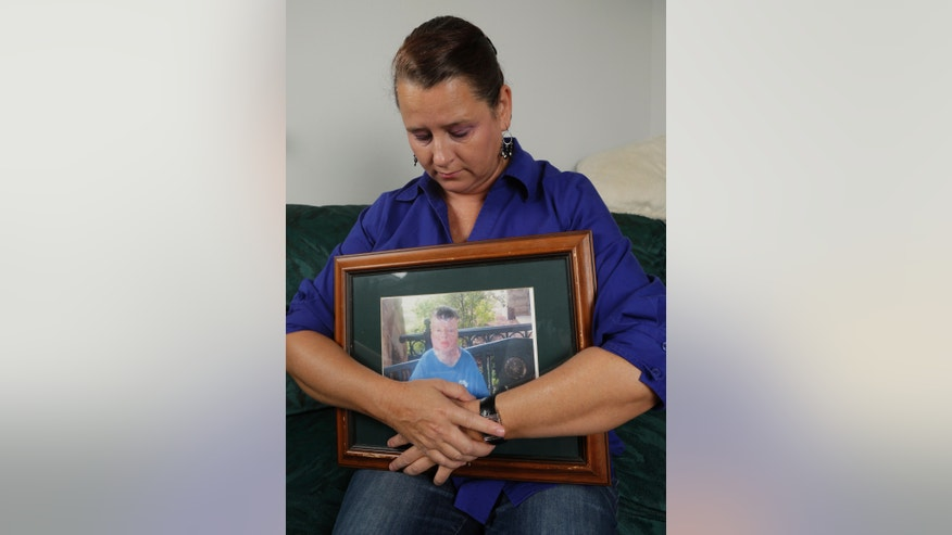 Colleen Middleton holds a photograph of her son, Robert, after an interview in Galveston, Texas on Thursday, Sept. 26, 2013. Robert was severely burned on his eighth birthday after being doused with gasoline, living for 13 years after the incident, but dying from skin cancer in 2011. A murder charge was filed Monday, Sept. 16, 2013, against suspect Don Willburn Collins, 28, who was 13 at the time of the burning. (AP Photo/David J. Phillip)