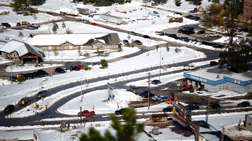 Oct. 7, 2013: Major roads are plowed, but piles of snow are melting causing potential flood hazards in Rapid City, S.D.. (AP/Rapid City Journal, Benjamin Brayfield)