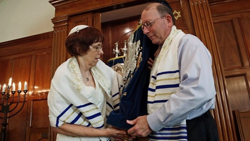 Oct. 2, 2013: In this photo, Rabbi Lynne Goldsmith and her husband Rob Goldsmith remove the Torah from the Ark inside Temple Emanu-El in Dothan, Ala. Faced with a dwindling, aging congregation, members of a south Alabama synagogue five years ago began recruiting Jews to move to Dothan with the promise of $50,000 in relocation assistance.
