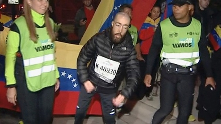 Oct. 14, 2013: Maickel Melamed, 38, center, of Venezuela, who has muscular dystrophy, nears the finish line to be the last runner to finish the Chicago Marathon.