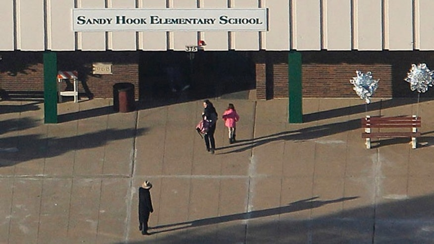 FILE 2013: A parent escorts her daughter into the former Chalk Hill School, a disused school refurbished specifically for the students from Newtown which now bears the name Sandy Hook Elementary School, in Monroe, Connecticut.