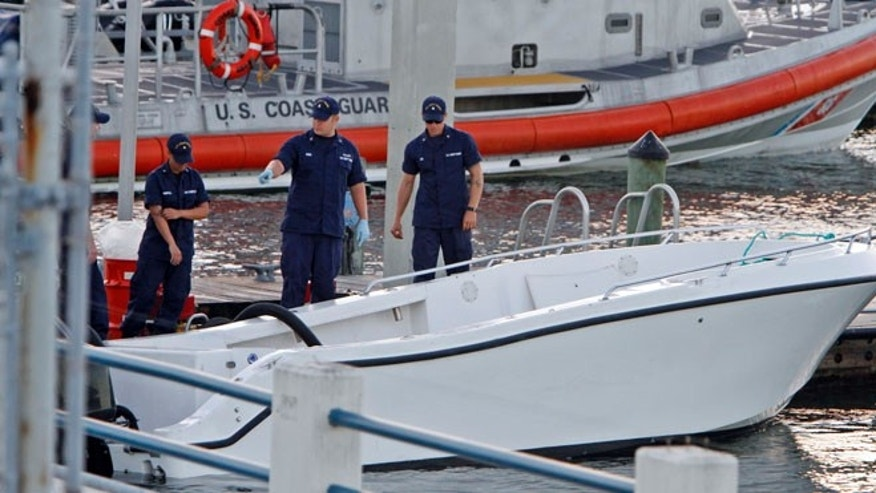 Oct. 16, 2013: U.S Coast Guard personnel inspects a vessel with a missing center console that capsized near Miami.