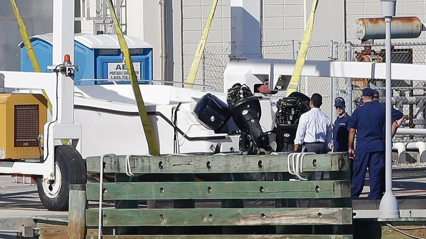 Members of the U.S. Coast Gard examine a small white boat, Wednesday, Oct. 16, 2013 at the U.S. Coast Guard Station Miami Beach, in Miami Beach, Fla. Four women died and 10 people were taken into custody after the boat with more than a dozen people aboard, including Haitian and Jamaican nationals, capsized early Wednesday in the waters off South Florida. It was overloaded and lacked lifejackets, according to the Coast Guard. (AP Photo/Wilfredo Lee)