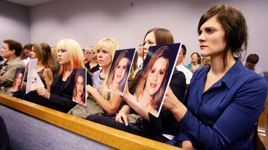 In this Aug. 27, 2012 file photo, family members hold photos of Michele MacNeill up facing as Martin MacNeill enters the court room in Provo, Utah.  Jury selection begins Tuesday, Oct. 15, 2013 in the case of Martin MacNeill, a Utah doctor accused of killing his wife, Michele MacNeill,  in 2007. Martin (AP Photo/The Deseret News, Scott G Winterton, Pool)