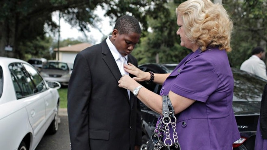 Wearing his only suit and with Bible in hand, Davion Only, 15, gets some last-minute help with his tie before walking into St. Mark Missionary Baptist church with Connie Going, his Eckerd case worker.