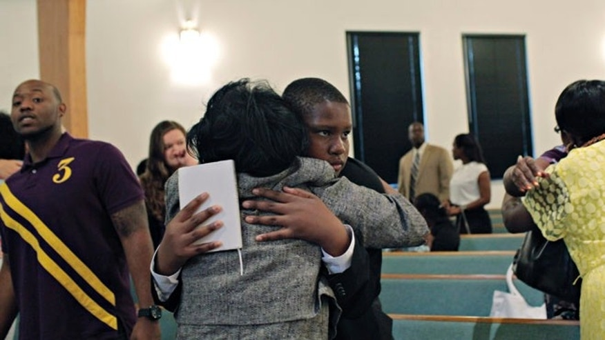 Davion Only, 15, center, gets a hug after he got up to speak about himself, and how badly he wants a family, at the close of a Sunday service at St. Mark Missionary Baptist Church.