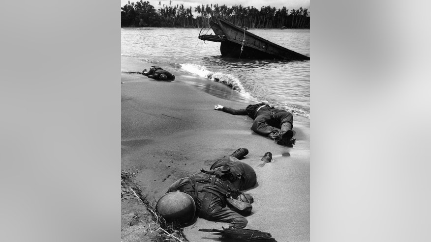 "Caption from LIFE magazine in 1943: ""Three dead Americans on the beach at Buna."""