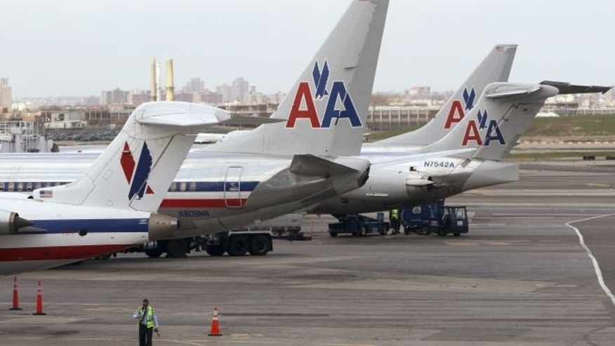 FILE: April 16, 2013: American Airlines aircraft sit on the tarmac at LaGuardia airport in New York. The FBI said Oct. 18 it has assigned its Joint Terrorism Task Force to lead a probe of recent laser attacks on the cockpits of two planes approaching the airport.