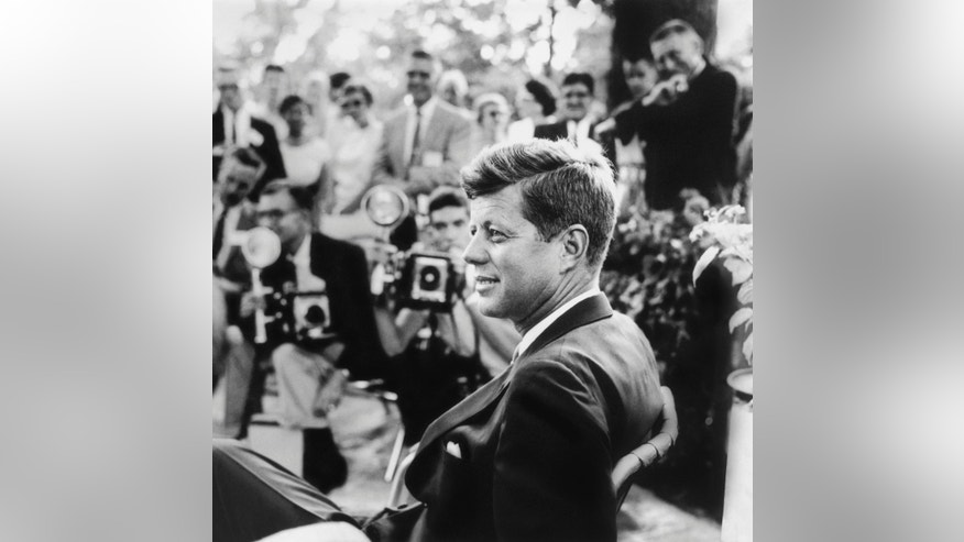 FILE - This handout photo provided by the Newseum, and the estate of Jacques Lowe, shows John F. Kennedy at a news conference in Omaha, Neb. in 1959.  Three cities loom large in the life and death of John F. Kennedy: Washington, D.C., where he served as U.S. president and as a senator; Dallas, where he died, and Boston, where he was born. With the 50th anniversary of his Nov. 22, 1963 assassination at hand, all three places are worth visiting to learn more about him or to honor his legacy.(AP Photo/Newseum, estate of Jacques Lowe)
