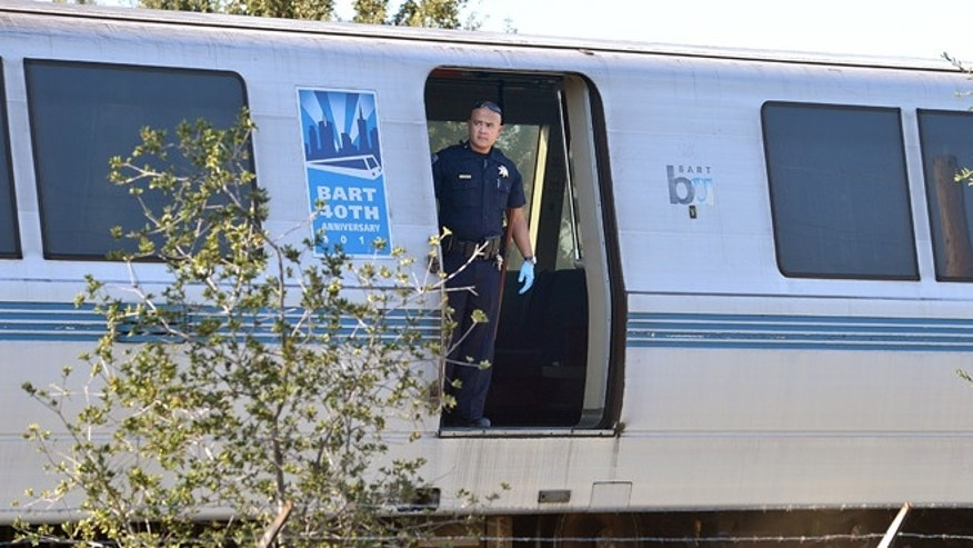 Oct. 19, 2013: A BART police officer looks out of a BART car that struck and killed two people along Jones Road in Walnut Creek, Calif.