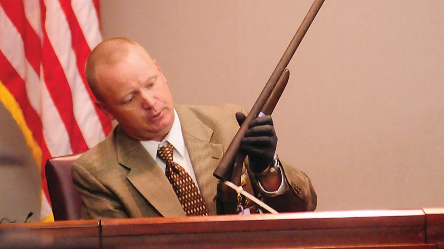 Glynn County Police Lt. Keith Stalvey shows the jury a shotgun taken from the trunk of the car Guy Heinze Jr. was driving when he returned home Aug. 29, 2009 to find his father and seven others dead in the trailer where lived with them, during Heinze's trial onWednesday, Oct. 16, 2013 in Brunswick, Ga.  Guy Heinze Jr. is charged with killing his father and seven other family members who shared a cramped mobile home just outside Brunswick. Heinze Jr. faces the death penalty if he's convicted of murder in the Aug. 29, 2009, slayings. (AP Photo/The Brunswick News, Michael Hall, Pool)