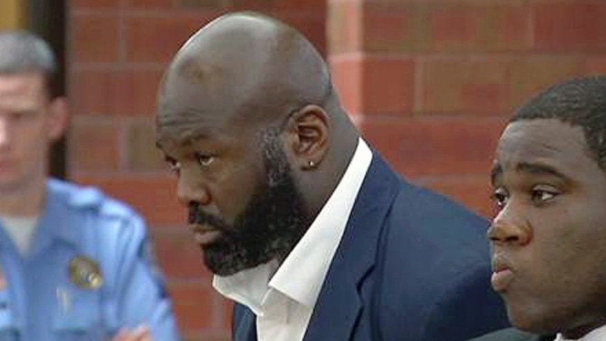 In this still image from video, former NFL defensive end Hugh Douglas, center, stands with his attorney, Corey Brinson, right, during arraignment in Superior Court on Monday, Oct. 21, 2013, in Hartford, Conn. Douglas, who played for the New York Jets, Philadelphia Eagles and Jacksonville Jaguars from 1995 to 2004,  has pleaded not guilty to charges he assaulted his girlfriend at a Hartford hotel.   (AP Photo/WFSB-TV, Peter McCue, Pool)