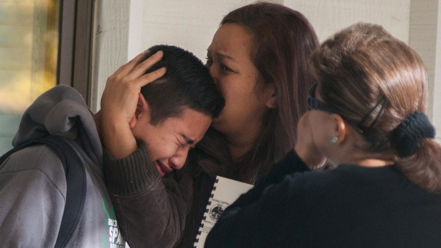 A  Sparks Middle School student cries and is comforted after being released from Agnes Risley Elementary School, where some students were evacuated to after a shooting at SMS in Sparks, Nev. on Monday, October 21, 2013 in Sparks, Nev. A  middle school student opened fire on campus just before the starting bell Monday, wounding two boys and killing a staff member who was trying to protect other children, Sparks police said Monday. The lone suspected gunman was also dead, though it's unclear whether the student committed suicide. (AP Photo/Kevin Clifford)