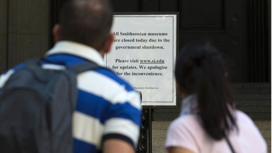 Oct. 1, 2013: Tourists read a sign informing visitors that all Smithsonian museums are closed due to the government shutdown outside the Smithsonian's National Museum of the American Indian in New York.
