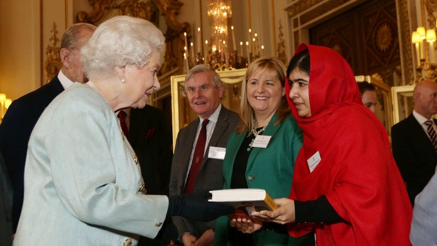 "FILE - In this Oct. 18, 2013, file photo Malala Yousafzai gives a copy of her book ""I Am Malala"" to Queen Elizabeth II of Great Britain during a reception for youth, education and the Commonwealth at Buckingham Palace, London. The 16-year-old girl from Pakistan, who was shot in the head by the Taliban last October for advocating education for girls, has inspired the development of school curriculum encouraging advocacy.  George Washington University announced Monday, Oct. 14, that faculty members are creating curriculum tools to accompany her book, and that several faculty members will pilot the curriculum early next year for both college and high school instruction. (AP Photo/Yui Mok, Pool)"