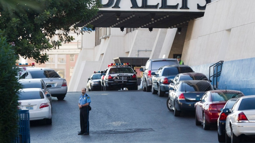 Las Vegas Metro Police cars and a hotel security officer are shown in front of Bally's hotel-casino after an early morning shooting left one person killed and two wounded in Drai's, a nightclub inside Bally's, in Las Vegas, Monday, Oct. 21, 2013. A suspect is in custody, police said. (AP Photo/Las Vegas Sun/Steve Marcus)