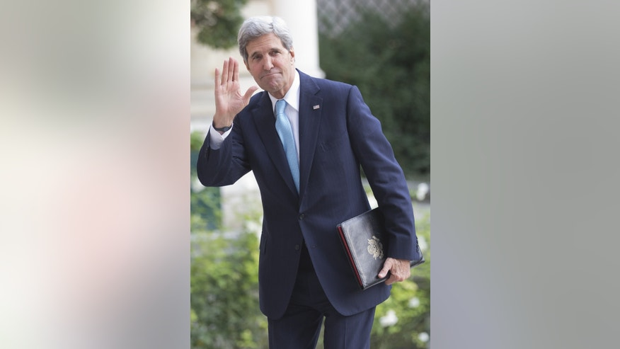U.S. Secretary of State John Kerry waves to the media as he arrives at the U.S. embassy for a meeting with the Arab League in Paris, Monday, Oct. 21, 2013. Kerry is in Paris for diplomatic talks about a peace process for Israel and Palestinian authorities. (AP Photo/Michel Euler)