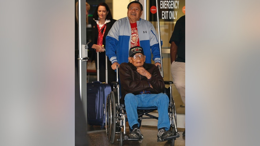 Phillip Coon, of Sapulpa, a 94-year-old World War II veteran who was a prisoner of war in Japan who survived the Bataan death march, is pushed in his wheelchair by his son Michael Coon, as a crowd of supporters greet Phillip as he returns home from Japan, at the Tulsa International Airport, in Tulsa, on Monday, Oct. 21, 2013.  (AP Photo/Tulsa World, Cory Young)