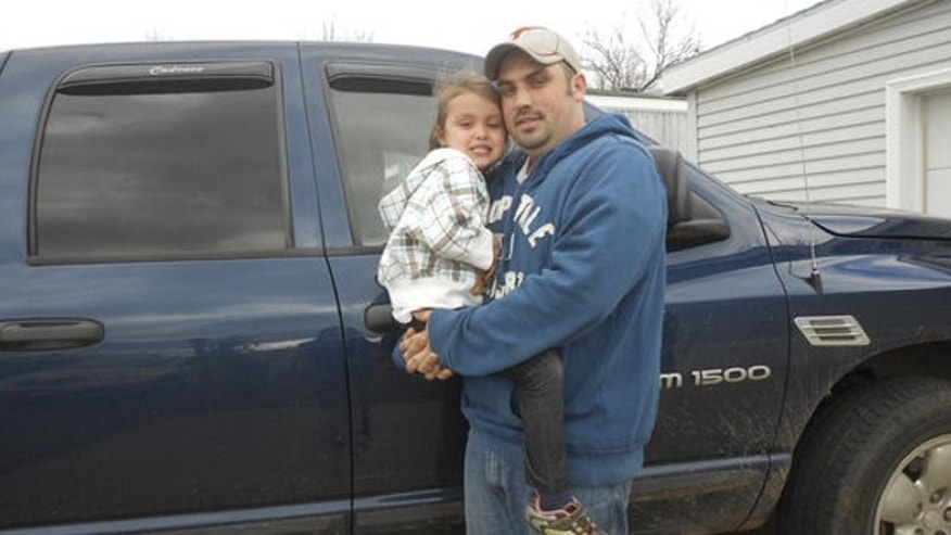UNDATED: Chris Lucas holds his daughter, Cadence, 4, in Iron Mountain, Mich., in this photo. When her father was knocked unconscious in an accident on Tuesday, Oct. 15, 2013, Cadence ran a quarter mile to their nearest neighbor to summon help.