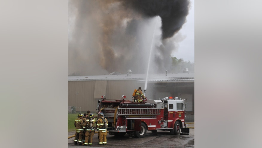 FILE - In this May 14, 2010 file photo, a firefighter sprays water on a fire at a gunpowder plant, in Colebrook, N.H. An explosion at the plant killed two people. The owner of the Black Mag plant, Craig Sanborn, 64, of Maidstone, Vt., was convicted of negligent homicide on Wednesday, Oct. 23, 2013. (AP Photo/The News and Sentinel, Karen Ladd, File)
