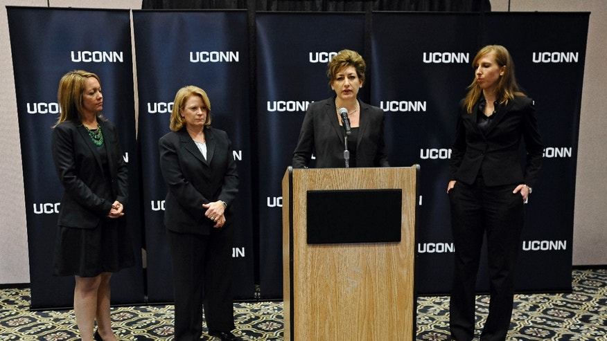 University of Connecticut President Susan Herbst, at podium, speaks to the media about the federal civil rights complaint filed Monday by seven women, as Associate General Counsel to the UConn Nicole Gelston, left, UConn Police Chief Barbara O'Connor, second from left, and UConn Title IX Coordinator Elizabeth Conklin, right, look on, Wednesday, Oct. 23, 2013, in Storrs, Conn. The seven women allege they were assaulted while attending UConn and that officials responded with deliberate indifference or worse. (AP Photo/Jessica Hill)